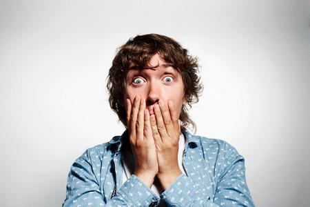 viso di uomo: Ritratto del primo piano di giovane uomo bello guardare sconvolto sorpreso in piena mani incredulità sul occhi aperti bocca, isolato su sfondo grigio. Positivo emozioni umane sensazione espressione facciale