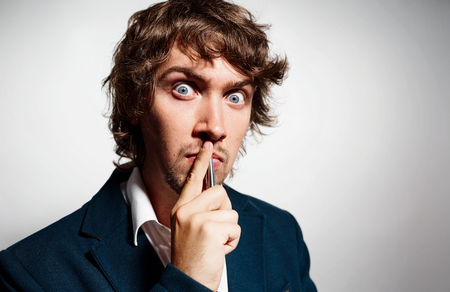 Closeup portrait young puzzled business man thinking deciding deeply about something finger on lips looking confused isolated grey background. Emotion facial expression, feeling, situation perception