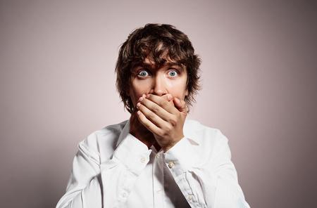 boca cerrada: Primer retrato de joven apuesto hombre de negocios sorprendido, joven hombre de negocios en silencio cubierta cerrada la boca observando. Emoción humana Negativo, facial símbolo expresión.