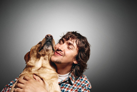 Closeup portrait handsome young hipster man, hugs his good friend dog isolated black grey background. Positive human emotions, facial expression, feelings.
