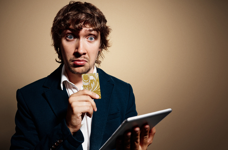 banking concept: Closeup portrait of handsome surprised business man looking at camera with tablet shopping on internet standing against gold background.