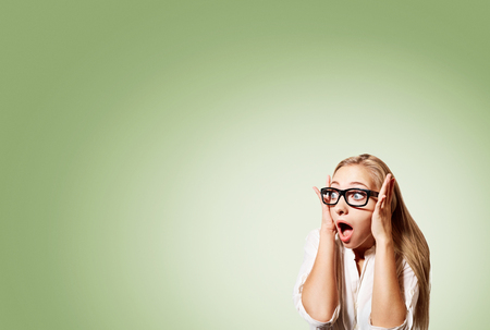 disbelief: Portrait of surprised young handsome blonde business woman looking shocked in full disbelief hands on head open eyes with glasses, isolated on pistachio background. Positive human emotion facial Stock Photo