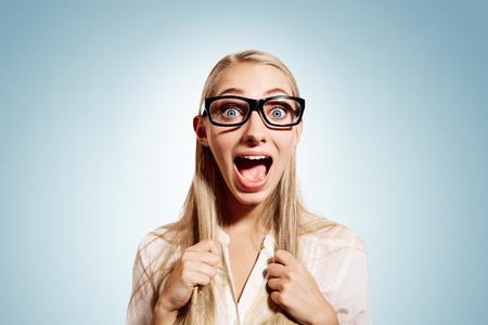 Close up retrato de joven mujer de negocios rubia, mirando sorprendido, sorprendido, incrédulo completa aislado fondo azul. Emociones humanas positivas, las expresiones faciales, el sentimiento, la actitud, la reacción Foto de archivo