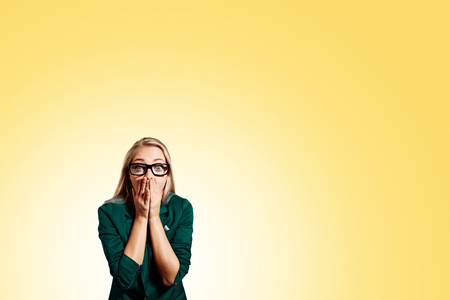 Portrait of surprised young handsome blonde business woman looking shocked in full disbelief hands on mouth open eyes with glasses, isolated on yellow background. Positive human emotion facial Imagens