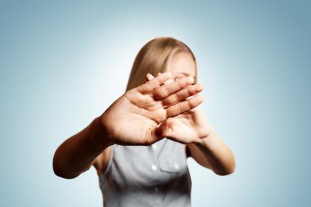 desconfianza: Primer desconfianza joven del retrato del retrato de la mujer rubia que cierra la mano de la cámara y no quiere ser fotografiado en fondo azul aislado. Las emociones negativas, la expresión facial