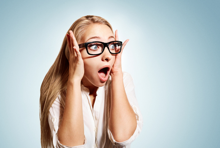 astonishment: Closeup portrait of surprised young handsome blonde business woman looking shocked in full disbelief hands on head open eyes with glasses, isolated on blue background. Positive human emotion facial