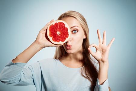 toronja: Mujer rubia joven con la toronja en su retrato manos estudio aislado sobre fondo azul. Mujer rubia joven que muestra signo de OK sobre los beneficios de la vitamina C Foto de archivo