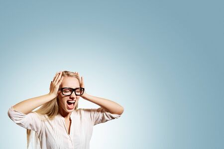 tired worker: Portrait upset stressed young blonde business woman squeezing her head, going nuts, screaming, losing her mind, looking up isolated blue wall background. Negative emotion feeling reaction