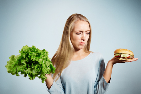 hesitating: Pensive woman making decision between healthy food and fast food, over blue background Stock Photo