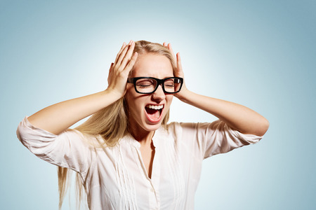 mind: Closeup portrait upset stressed young blonde business woman squeezing her head, going nuts, screaming, losing her mind, looking up isolated blue wall background. Negative emotion feeling reaction