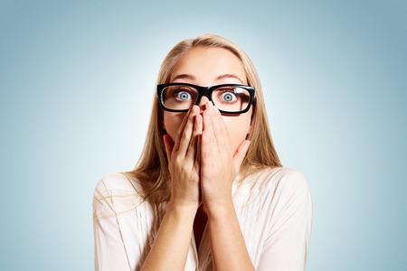 femme bouche ouverte: Portrait of surpris beau jeune femme d'affaires blonde regardant choqu� dans les mains pleines incr�dulit� sur la bouche les yeux ouverts avec des lunettes, isol� sur fond bleu. �motion humaine positive du visage