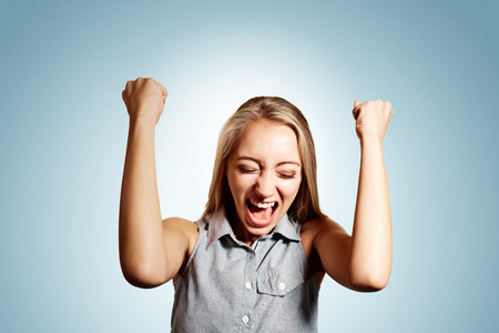 jubilation: Pretty young blonde woman throwing her arms up into the air and laughing in jubilation at her success or victory.