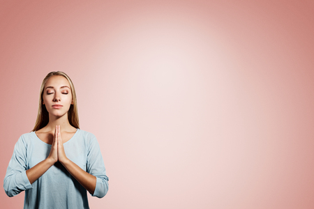jesus adolescent: Closeup portrait of a young blonde woman praying with closed eyes isolated on pink background Stock Photo