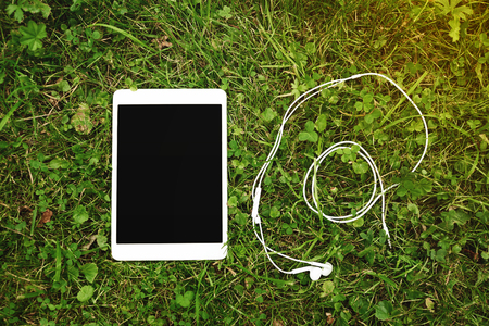 blank tablet: Digital tablet with blank screen and headphone lying on the grass. Stock Photo