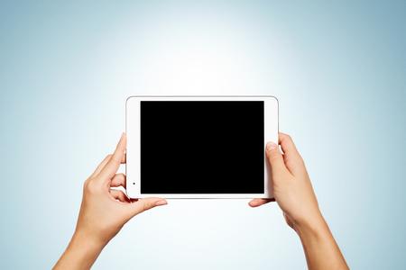 Vrouw handen houden hedendaagse generieke tablet pc met een leeg scherm. Geïsoleerd op een blauwe achtergrond.