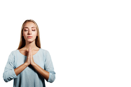 Closeup portrait of a young blonde woman praying with closed eyes isolated on white background Banco de Imagens