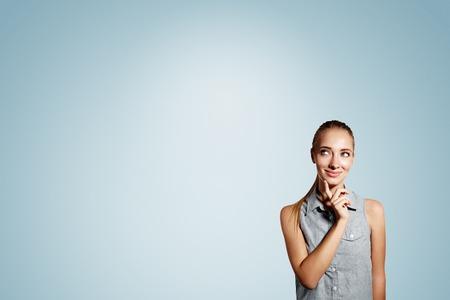 Portret van de knappe jonge nadenkende blonde vrouw die over blauwe achtergrond