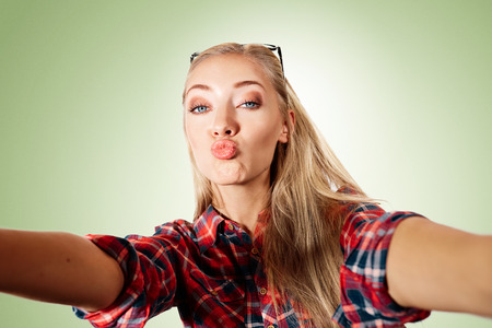 duck: Close up portrait of a young kissing blonde girl holding a smartphone digital camera with her hands and taking a selfie self portrait of herself standing against blue background
