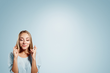 good wishes: Close-up portrait of a beautiful woman closing her eyes, crossing her fingers hoping for the best,isolated on blue background Stock Photo