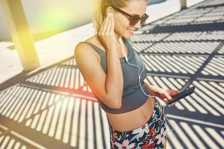 escuchando musica: Close up retrato de la aptitud joven rubia en ropa deportiva escuchando música con auriculares después del entrenamiento al aire libre en hermoso día soleado.