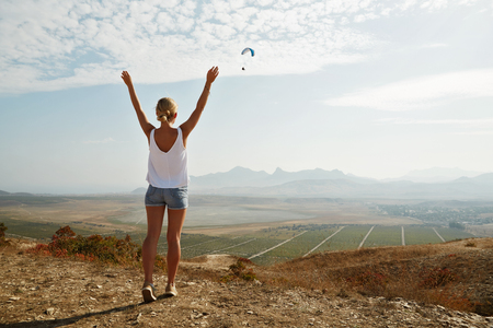 arms above head: Happy celebrating winning success woman at sunset or sunrise standing elated with arms raised up above her head in celebration of having reached mountain top summit goal during hiking travel trek