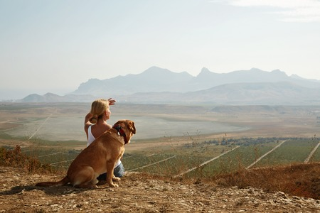 dog owner: Beautiful girl with dog on the mountain top.