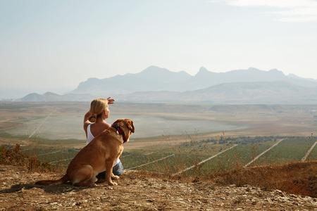 mujer con perro: Hermosa chica con el perro en la cima de la montaña. Foto de archivo