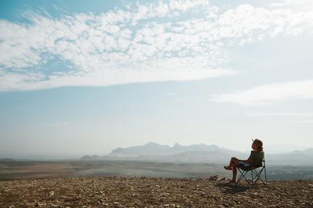 Young tourist girl relaxing on rock and enjoying beautiful view Banco de Imagens