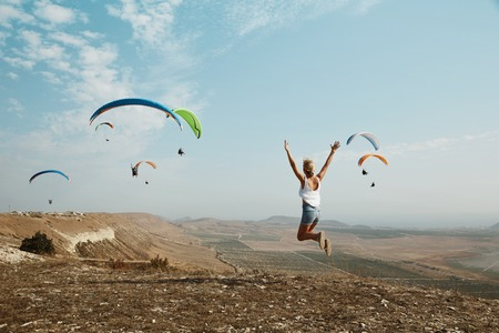 joyfully: Young women joyfully jumping with glider in background. Stock Photo
