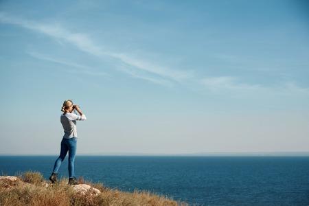 Woman tourist looking through binoculars at distant sea, enjoying landscape