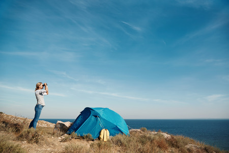 mochila de viaje: Hembra joven activo de pie en la cima de la montaña y mirando lejos en binocular, el estilo de vida extrema, los viajes y el concepto de viaje