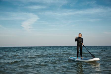 若いブロンドの女性のパドルで海 paddleboard