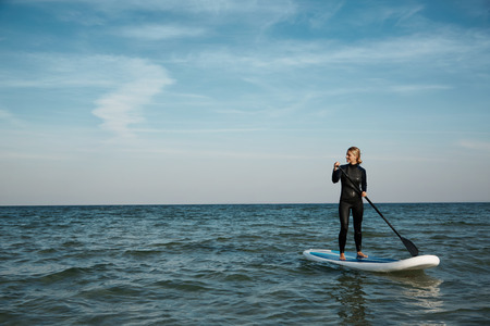 paddles: Young blonde female paddles a paddleboard at the sea