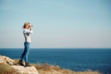 Woman tourist looking through binoculars at distant sea, enjoying landscape