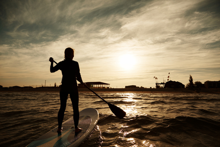silhouette of young girl paddleboarding at sunset, recreation sport paddling ocean beach surf orange sunlight reflection hue on water