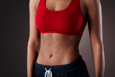 woman posing: Beautiful mixed race sporty woman with slim stomach isolated over background Stock Photo