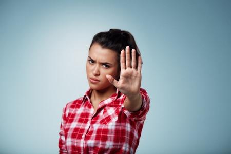 怒っている女性隔離されたバック グラウンド上のジェスチャー一時停止の標識。手に焦点を当てる