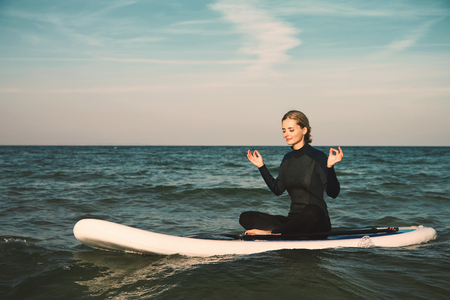 Stand up paddle board yoga performed by beautiful girl on the bright sunset background, yoga training on the beach