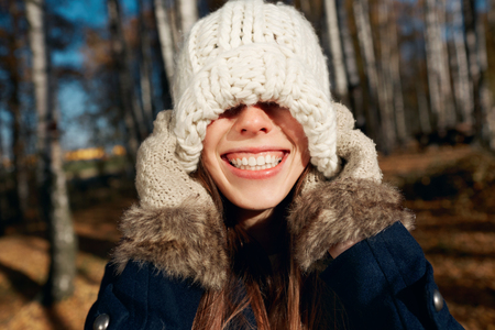 �aucasian: Excited happy fall woman smiling joyful and blissful pull knitted hat outside in colorful fall forest. Beautiful energetic ?aucasian young woman Stock Photo