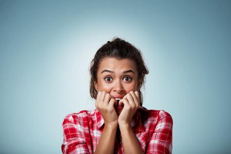 sorpresa: Close-up retrato de una mujer joven asustada, temerosa y ansiosa mordiéndose las uñas de los dedos, mirando a la cámara con los ojos bien abiertos aislados en un fondo azul. Las emociones humanas