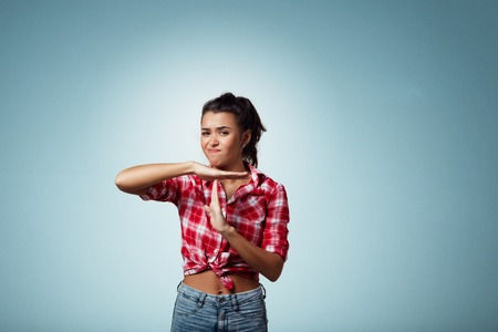 out time: Closeup portrait of attractive young serious woman showing time out gesture with hands, isolated on blue background. Negative human emotion facial expression sign symbols,body language attitude