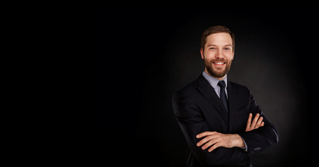 Young handsome businessman in a suit with great smile against black background with lots of copy space