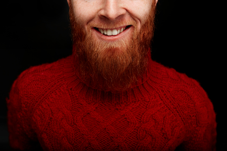 stylish man: Closeup portrait  of long red beard and mustache man smiling in a red knitted sweater isolated on black background