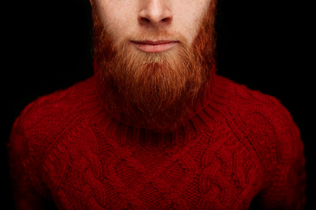 long hair boy: Closeup portrait  of long red beard and mustache man smiling in a red knitted sweater isolated on black background