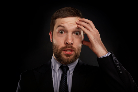 disbelief: Closeup portrait of handsome bearded businessman looking shocked, surprised in disbelief, with hands on face looking at you camera, isolated on background. Positive human emotions, facial expressions