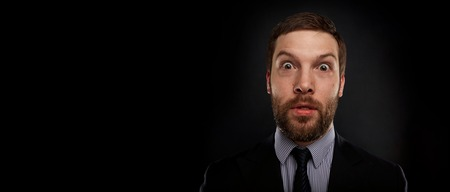 disbelief: Closeup portrait of happy young handsome businessman looking shocked surprised in full disbelief open mouth eyes, on black background. Positive human emotion facial expression feeling reaction Stock Photo