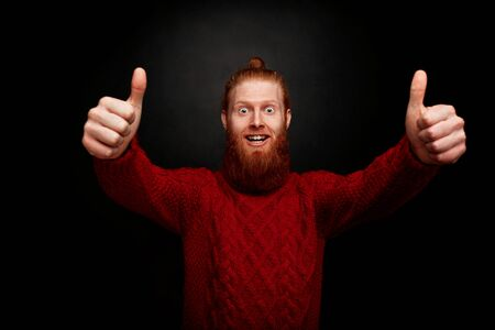 satisfying: Smiling bearded man showing thumb-ups. Happy man in red knitted sweater satisfying his lifestyle on black background