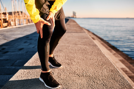 lesionado: Lesión de la rodilla - Deportes que funcionan con lesiones de rodilla en el hombre. Cerca de las piernas, el músculo y la rodilla al aire libre. corredor aptitud atleta masculino con el dolor de la rodilla esguince