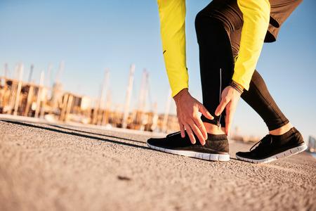 Broken tobillo torcido - corriendo lesión deportiva. Corredor del hombre atlético de sus pies tocando en el dolor debido a la lesión en el tobillo Foto de archivo