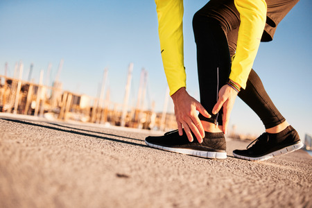 ankles: Broken twisted ankle - running sport injury. Athletic man runner touching foot in pain due to sprained ankle